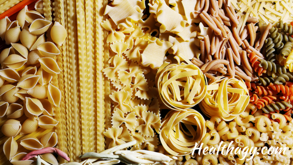 pasta in different shapes and colors, long and thin, spirals, shells, and short and round.  Colors include ivory, gold, red, green, browns.